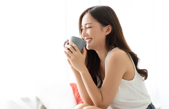 Happy smiling beautiful Asian woman awaking with cup of coffee at bedroom with Eyes Closed. People Lifestyle concept;