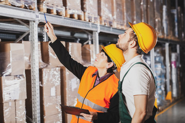 Two warehouse workers in green uniforms and yellow safety helmets
