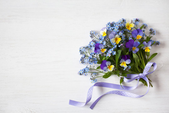 A bouquet of forget-me-nots and pansies on a wooden background
