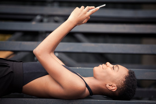 Side view of woman using smart phone while lying on bleacher in park