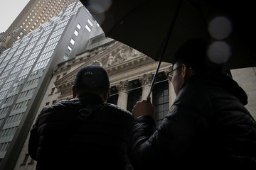 People photograph the front of the NYSE during a rainy day in New York