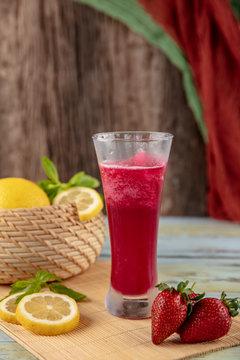 Tasty strawberry lemonade with ice in mason jar, closeup. Summer season beverage concept
