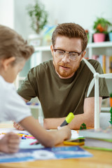 Focused good-looking ginger teacher working on poster