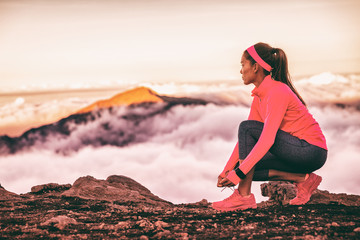 Athtlete tying laces of running shoes wearing wearable tech device smartwatch watch for fitness and sports. Trail runner woman getting ready to run on mountains nature landscape in sunset clouds. Wall mural