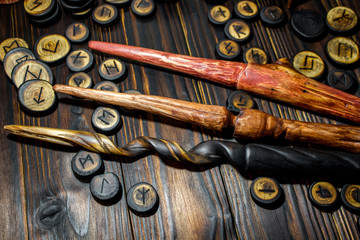 Homemade magic wands and wooden runes on a dark wooden background