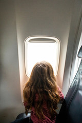 A toddler aged girl looking out the window of a plane.
