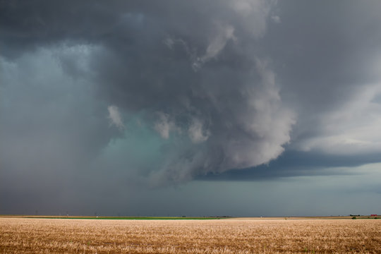 A severe supercell storm containing rain, hail, and damaging winds approaches over farmland.