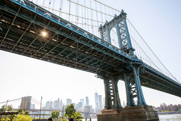 A view from below of the Manhattan Bridge on the Brooklyn waterfront with the city of New York in the background.