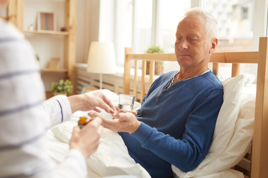 Portrait of senior man lying in bed and taking pills with caring wife or nurse , copy space