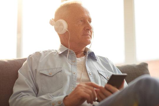 Portrait of modern senior man wearing headphones using smartphone sitting on sofa at home lit by sunlight