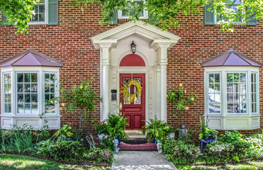 Entrance with columns and bay windows of beautiful two-story brick house with pots of flowers and yellow climbing roses and headplanters and ferns frame by Maple tree limbs Wall mural