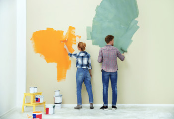 Young couple painting wall indoors. Home repair Wall mural