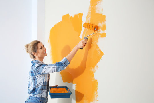 Happy woman painting wall indoors, space for text. Home repair