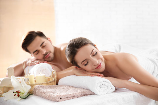 Young couple with spa essentials in wellness center