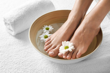 Photo sur Plexiglas Pedicure Closeup view of woman soaking her feet in dish with water and flowers on white towel, space for text. Spa treatment
