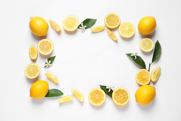 Frame made of lemons, leaves and flowers on white background, top view with space for text. Citrus fruits Wall mural