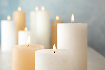 Burning candles on table against color background, closeup