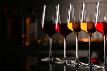 Spoed Foto op Canvas Alcohol Row of glasses with different wines on bar counter against blurred background. Space for text