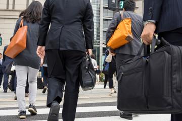 横断歩道を渡るビジネスマンの後ろ姿