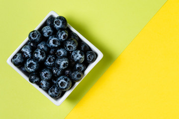 Fresh blueberries inside ceramic pot on green and yellow background.