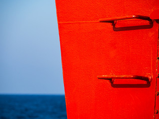 Red railing steps on a ship - high contrast image - sky and sea in the background