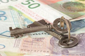 Ein Schlüssel, und Geldscheine Polnische Zloty und Schweizer Franken