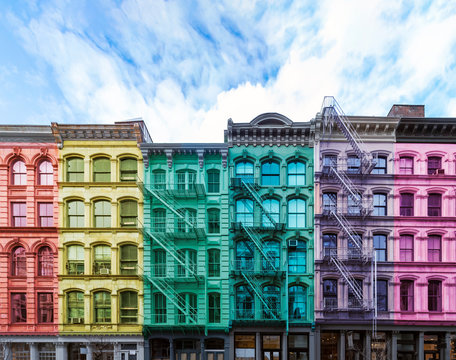 Rainbow colored block of old buildings in the SoHo neighborhood of Manhattan in New York City with blue sky background above