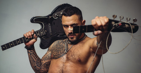 guitar player at rock concert. sexy abs of tattoo man hold broken electro guitar. sport and fitness. brutal sportsman torso. steroids. confidence charisma. muscular macho man with athletic body