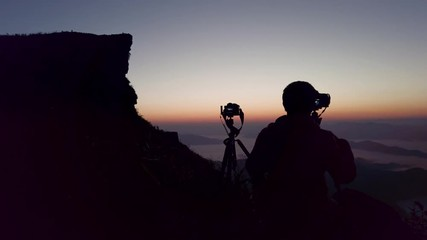Wall Mural - silhouette of Photographer take a photo at sunset on mountains.
