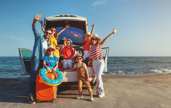 happy large family  in summer auto journey travel by car on beach.