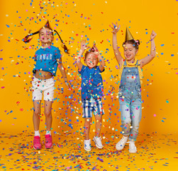 happy children on holidays  jumping in multicolored confetti on yellow