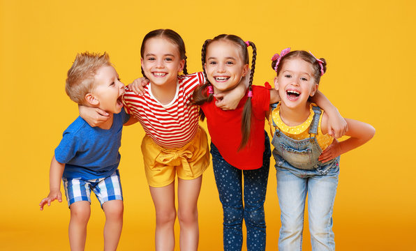 group of cheerful happy children on colored yellow background.