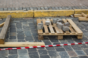 Lay granite cubes on a pallet at the stone road. Reconstruction of sidewalk with cobblestone