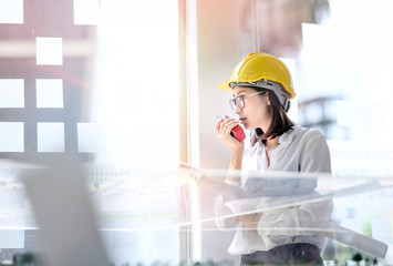 Woman engineer wearing yellow helmet , holding blueprint standing in office and talking on the radio.