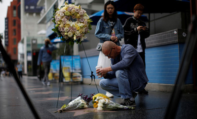 A person kneels by the star of late actor Doris Day on the Hollywood Walk of Fame in Los Angeles