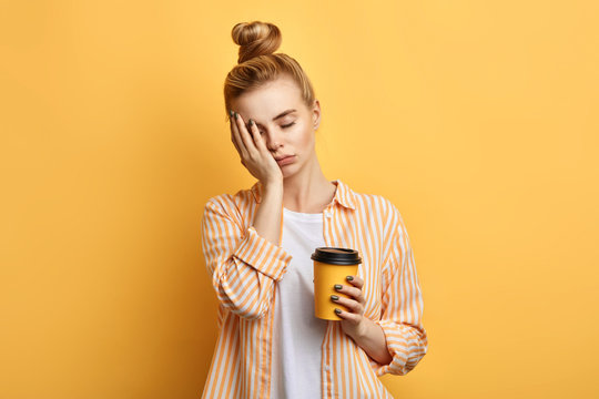 Tired sleepy woman holds a cup of coffee, has sad expression, closes eyes, cannot wake up in the morning and go to work. difficult, hard monday. isolated yellow background