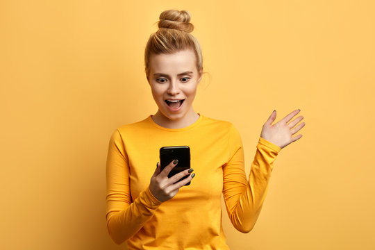 shocked young emotional girl looking at mobile phone isolated over yellow background. close up photo. woman has read interesting information form the gadget.