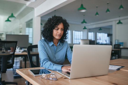 Focused young businesswoman using a laptop at her office desk