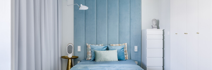 Bedroom with blue upholstered wall