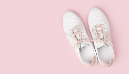 White leather sneakers with laces isolated on pink background