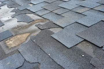 Сlose up view of bitumen shingles roof damage that needs repair.