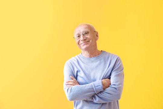 Portrait of happy elderly man on color background