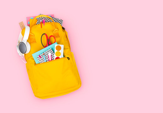 Yellow backpack with school supplies isolated on pink background