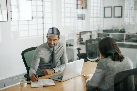 Smiling manager taking notes while conducting an office interview