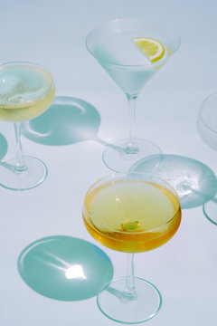 Three cocktails with shadows over light blue background