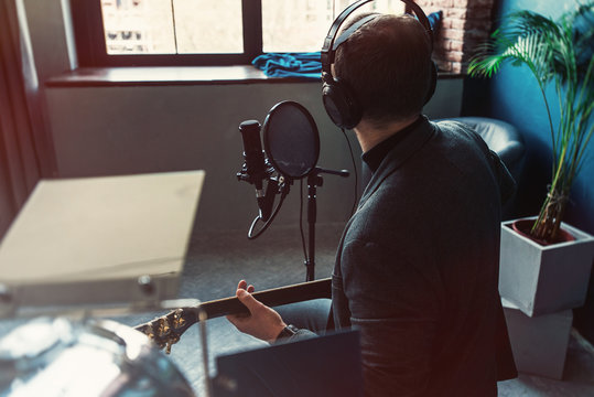 Close up of a man singer sitting on a stool in a headphones with a guitar recording a track in a home studio