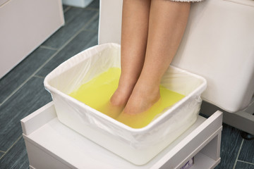 Woman feet in spa  bowl with yellow water