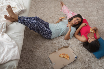 Top view of two smiling young girls lying on the floor in their house eating pizza and talking