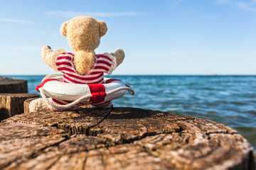 Happy Holiday at Sea / Teddy bear sitting on wooden breakwater at seaside, enjoy sunny day in nostalgic bathing suit with life buoy (copy space)