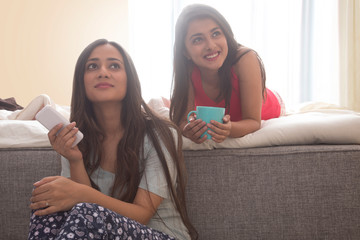 Two smiling young girls at home relaxing holding coffee cup and mobile phone